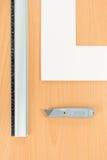 De snijdersuitrusting van de mat. Heerser, mes op houten achtergrond Stock Foto's