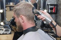 De snijmachine van het kappershaar De meester verstrekt een kapsel royalty-vrije stock afbeelding