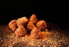 De snoepjes van de chocoladetrofee op een zwarte achtergrond met cacao stock foto
