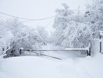 De snow-covered weg wordt gesloten door een barrière en het is onmogelijk over te gaan stock foto