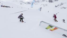 De Snowboarderdia op ijzersleep op helling keert zich om cameraman SNEEUW BERGEN competition Mensen stock videobeelden