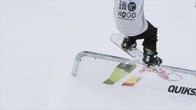 De Snowboarderdia op ijzersleep op helling keert zich om cameraman SNEEUW BERGEN competition wedstrijd stock videobeelden