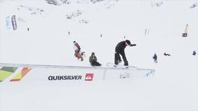 De Snowboarderdia op ijzersleep op helling, maar ontbreekt Landschap van sneeuwbergen competition stock video