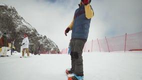 De Snowboardergolf dient camera, rit op helling bij sneeuwsleep in eenvormig Mensen Het van brandstof voorzien van de benzinepomp stock footage