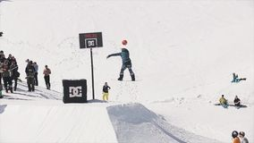 De Snowboarderrit op springplank werpt bal in basketbalmand Mensen ontbreek stock footage