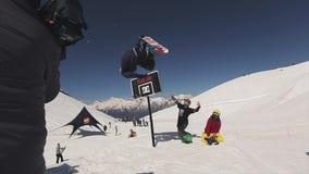 De Snowboardersprong op springplank maakt salto mortale in lucht De mand van het basketbal Zon stock video