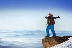 De Snowboardertribunes in winnaar stellen op de bovenkant van berg stock afbeelding