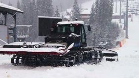 De Snowcatwerken aangaande een berghelling bij de ski stock video