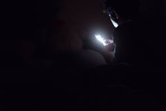 De sociale media wijden zich, Mensen op bed niet slaap omdat spel slimme telefoon na het uitzetten van de vage lichten donkere ru Stock Afbeelding