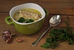 De soep, de peterselie en het knoflook van de kippennoedel op een houten lijst Royalty-vrije Stock Afbeeldingen
