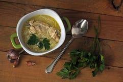 De soep, de peterselie en het knoflook van de kippennoedel op een houten lijst Stock Fotografie