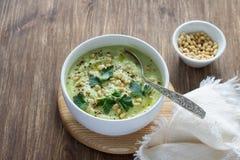De soep van de bloemkoolpuree met peterselie en pijnboomnoten Stock Afbeelding