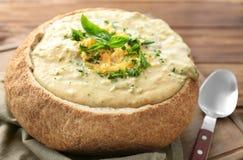 De soep van de broccolicheddar in broodkom stock afbeeldingen