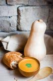 De soep van de Butternutpompoen met eigengemaakt brood op houten achtergrond Stock Foto
