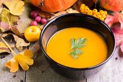 De soep van de de herfstpompoen op natuurlijk bureau en kleurrijke achtergrond royalty-vrije stock fotografie