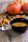 De soep van de de herfstpompoen op natuurlijke houten lijst stock afbeelding