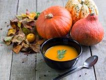 De soep van de de herfstpompoen in zwarte kom op natuurlijke houten lijst royalty-vrije stock foto's