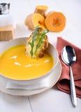 De soep van de pompoenroom met parmezaanse kaastoost in een witte plaat Royalty-vrije Stock Afbeelding