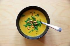 De soep van de Puréedwortel in kom met pompoenzaden en peterselie Stock Foto's