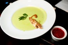 De soep van de groene erwtenroom met koninklijke garnalen stock afbeelding