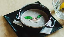 De soep van de paddestoelroom met kruiden en kruiden in een zwarte kom stock afbeelding