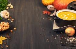 De soep van de pompoenroom in een donkere ceramische pan op de donkere achtergrond Stock Afbeelding