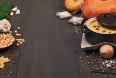 De soep van de pompoenroom in een donkere ceramische pan op de donkere achtergrond Stock Fotografie