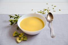 De soep van de pompoenroom met pompoenzaden in witte platen met een zilveren lepel stock foto