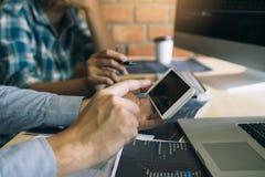 De softwareontwikkelaars gebruiken smartphones en analyseren samen de code in het programma over de computer wordt geschreven die royalty-vrije stock afbeelding