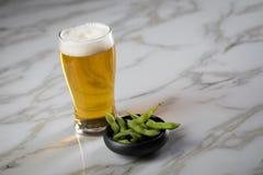 De sojabonen van gedeelte werpen de Japanse Edamame in porselein met bierglas op marmeren achtergrond royalty-vrije stock afbeelding