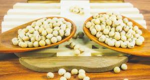 De sojaboon in houten lepelhoogtepunt op houten achtergrond, Macroschot van sojabonen vult het kader Stock Foto