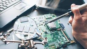De soldeerboutlaptop van de technicusreparatie computer stock foto's