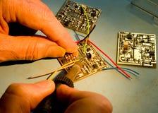 De solderende draden van de ingenieur aan een kringsraad. Royalty-vrije Stock Foto's