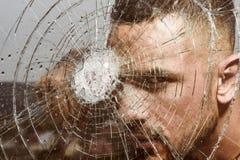 De, som bor i glashus, bör inte kasta stenar Stark man som ner knackar en glasvägg med den stiliga latinoen för näve royaltyfri foto