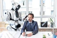 De sombere werknemer werkt met robot Royalty-vrije Stock Fotografie