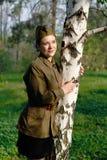 De sovjet vrouwelijke militair in eenvormig van Wereldoorlog II bevindt zich dichtbij de berk royalty-vrije stock afbeelding