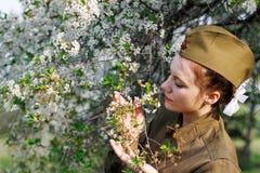 De sovjet vrouwelijke militair in eenvormig van Wereldoorlog II bevindt zich dichtbij bloeiende boom stock fotografie