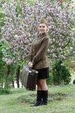 De sovjet vrouwelijke militair in eenvormig van Wereldoorlog II met koffer bevindt zich op een stomp die dichtbij boom bloeien royalty-vrije stock foto