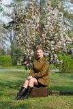 De sovjet vrouwelijke militair in eenvormig van Wereldoorlog II zit op een koffer die dichtbij boom bloeien stock foto