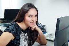 De Spaanse donkerbruine zitting van de bureauvrouw door bureau en Stock Foto