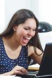 De Spaanse donkerbruine zitting van de bureauvrouw door bureau en Royalty-vrije Stock Foto
