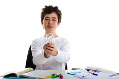 De Spaanse jongen houdt een lightbulb terwijl het doen van thuiswerk royalty-vrije stock foto's
