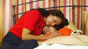 De Spaanse moeder neigt aan haar veel liefs weinig dochter die ziek is stock videobeelden