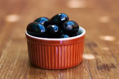 De Spaanse organische zwarte olijven van keukentapas in een bruine kleischotel Houten lijstachtergrond, zachte selectieve nadrukf Royalty-vrije Stock Afbeeldingen