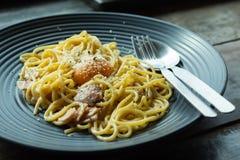 De spaghetti, gebraden kaas op een zwarte plaat op de lijst royalty-vrije stock afbeelding