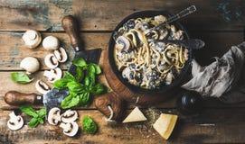 De spaghetti van paddestoeldeegwaren in ijzerpan met parmezaanse kaas, basilicum wordt gediend dat royalty-vrije stock foto
