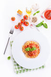 De spaghetti van tomatendeegwaren met verse tomaten, het basilicum, de Italiaanse kruiden en de olijfolie in een wit werpen op ee Stock Foto