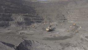 De spanwijdte van de hommel in een carrière bij de bodem Ijzerertsmijnbouw Graafwerktuigen en BelAZ-het werk stock video