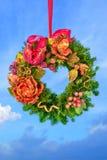 De sparrenkroon van Kerstmis die over blauwe hemel wordt gehangen Stock Foto's