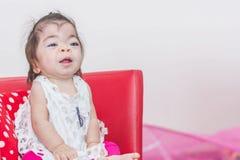 De speciale zoete Aziatische zitting van het babymeisje op stoel royalty-vrije stock afbeelding